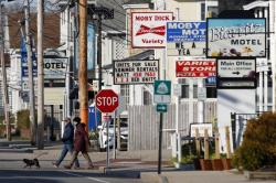 In this April 29, 2020 photo, a couple walks by a row of closed motels, in Old Orchard Beach, Maine