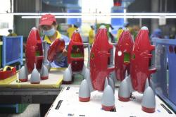 In this May 27, 2020, photo released by Xinhua News Agency, a worker makes plastic toys at a factory in Zhangjiajie, central China's Hunan Province