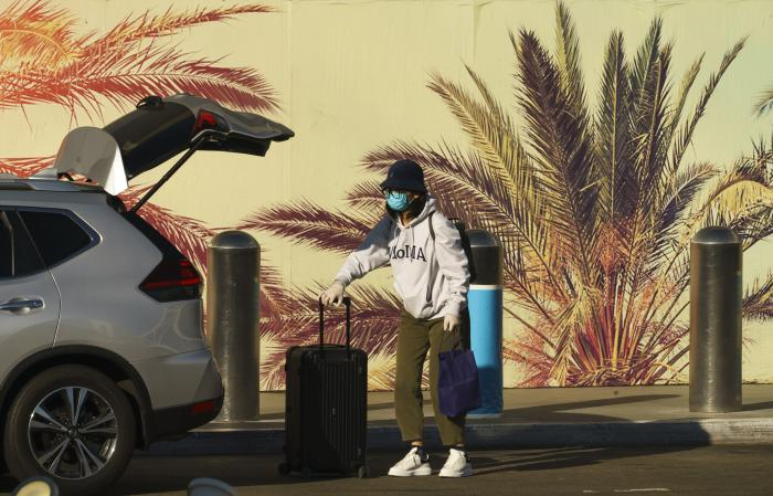 A traveler wears a face mask and gloves at Los Angeles International Airport in Los Angeles.