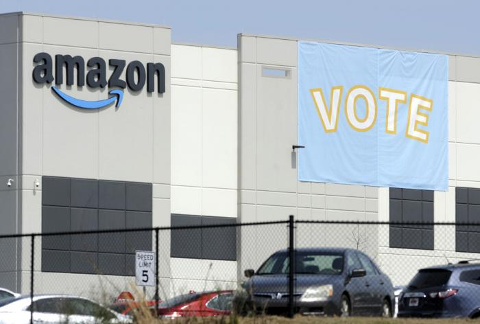 In this Tuesday, March 30, 2021 file photo, a banner encouraging workers to vote in labor balloting is shown at an Amazon warehouse in Bessemer, Ala