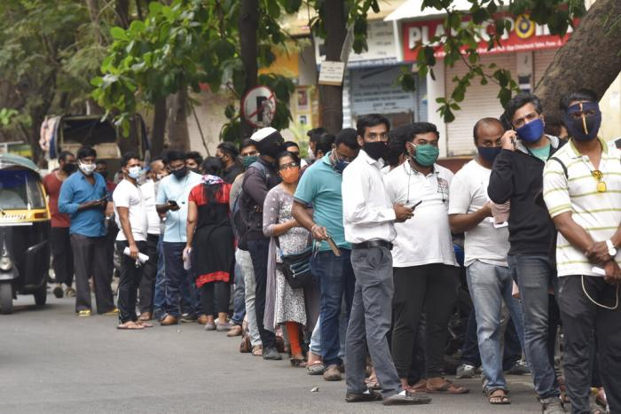 People wait in queues outside the office of the Chemists Association to demand necessary supply of the anti-viral drug Remdesivir, in Pune, India.