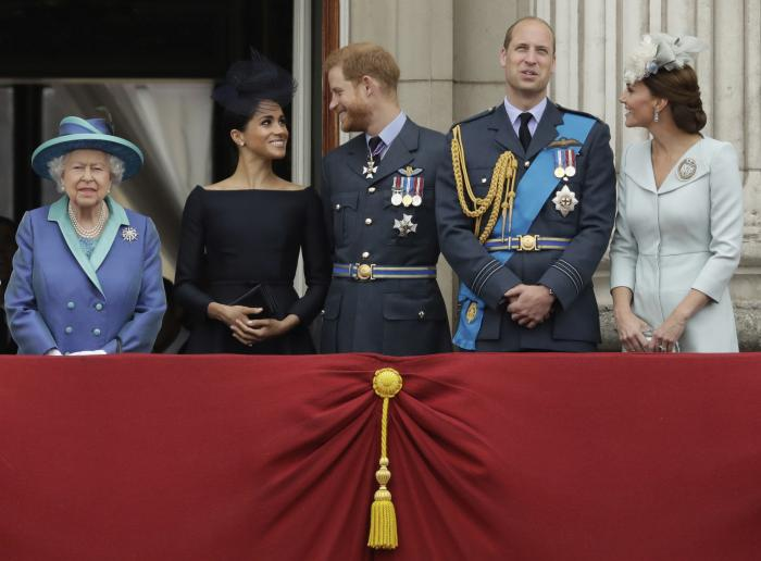 Britain's Queen Elizabeth II, and from left, Meghan the Duchess of Sussex, Prince Harry, Prince William and Kate the Duchess of Cambridge, watch as Royal Air Force aircraft pass over Buckingham Palace in London.