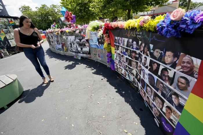 A visitor looks over a display with the photos and names of the 49 victims that died at the Pulse nightclub memorial Friday, June 11, 2021, in Orlando, Fla.