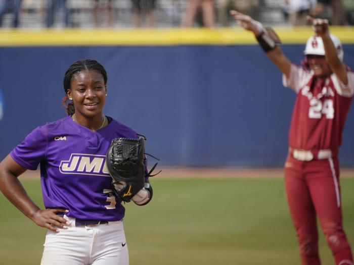 James Madison starting pitcher Odicci Alexander (3) stands in the pitching circle as Oklahoma's Jayda Coleman (24) celebrates at second base behind her after hitting a double in the fifth inning of an NCAA Women's College World Series softball game Monday, June 7, 2021, in Oklahoma City