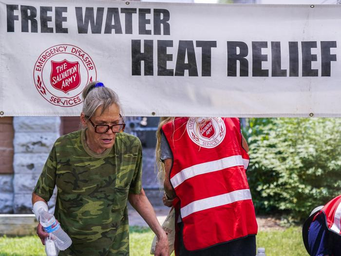 In this Tuesday, June 15, 2021, file photo, a pedestrian holds a bottle of cold water at a Salvation Army hydration station during a heatwave as temperatures hit 115-degrees in Phoenix