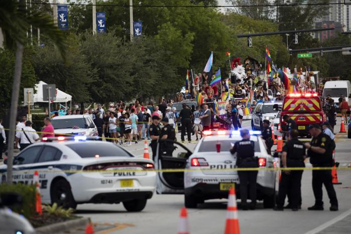 Police and firefighters respond after a truck drove into a crowd of people injuring them during The Stonewall Pride Parade and Street Festival in Wilton Manors, Fla., on Saturday, June 19, 2021